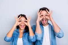 Fermez-vous vers le haut de la photo des couples créatifs et fous attrayants faisant le binocu Images libres de droits