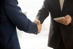 Fermez-vous vers le haut de la photo des hommes d'affaires informatiques se serrant la main Images libres de droits