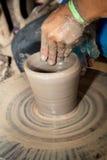 Fermez-vous vers le haut de la photo des mains d'enfant dans le métier de potier Photographie stock