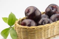 Fermez-vous vers le haut de la photo des prunes foncées dans un panier sur le blanc Photos stock
