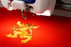 Fermez-vous vers le haut de la photo du logo de lion de machine et d'or de broderie sur le tissu rouge Photos stock