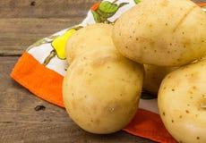 Fermez-vous vers le haut de la photo du tas des pommes de terre sur le tissu avec du bois Image libre de droits