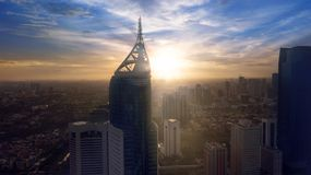 Fermez-vous vers le haut de la photo de silhouette d'un immeuble de bureaux moderne dedans au lever de soleil Images libres de droits