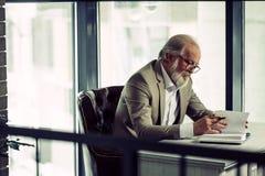 Fermez-vous vers le haut de la photo de vue de côté de l'homme d'affaires mûr travaillant dans le bureau moderne Images stock