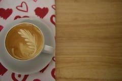 Fermez-vous vers le haut de la photographie de boissons d'une tasse de café chaude fraîche sur une nappe rouge de modèle de coeur Image stock