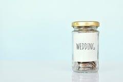 Fermez-vous vers le haut de la pièce de monnaie dans le pot en verre sur le fond bleu, concept épargnent l'argent Image libre de droits