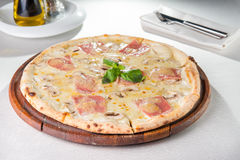 Fermez-vous vers le haut de la pizza délicieuse avec le lard, le fromage de champignon et fondu coupé en tranches sur le conseil  Images stock