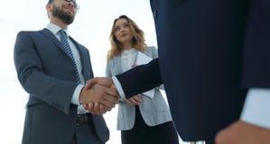 Fermez-vous vers le haut de la poignée de main d'homme d'affaires ensemble sur le lieu de réunion Photos stock