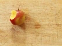 Fermez-vous vers le haut de la pomme rouge avec une morsure sur un conseil en bois d'en haut photo libre de droits