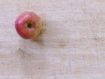 Fermez-vous vers le haut de la pomme rouge sur un conseil en bois d'en haut photo libre de droits