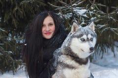 Fermez-vous vers le haut de la propriétaire heureuse de femme et du chien enroué dans le jour d'hiver Photographie stock libre de droits