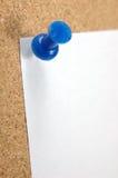Fermez-vous vers le haut de la punaise avec la note blanc sur le corkboard Photo stock