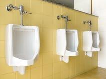 Fermez-vous vers le haut de la rangée des hommes blancs extérieurs d'urinoirs sur le jaune du publ de mur Image stock