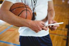 Fermez-vous vers le haut de la section médiane de l'entraîneur masculin utilisant le comprimé numérique image libre de droits