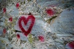 Fermez-vous vers le haut de la silhouette de graffiti de fond du coeur rouge sur un mur en pierre de vieux soulagement Images stock