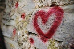 Fermez-vous vers le haut de la silhouette de graffiti de fond du coeur rouge sur un mur en pierre de vieux soulagement Image libre de droits