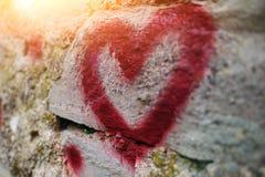Fermez-vous vers le haut de la silhouette de graffiti de fond du coeur rouge sur un mur en pierre de vieux soulagement Photo libre de droits