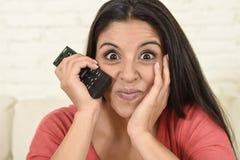 Fermez-vous vers le haut de la télévision de observation à la maison de jeune belle femme espagnole de portrait sur enthousiaste  Image stock