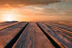 Fermez-vous vers le haut de la table en bois supérieure et brouillez le fond de coucher du soleil Images libres de droits