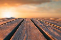 Fermez-vous vers le haut de la table en bois supérieure et brouillez le fond de coucher du soleil Photos stock