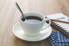 Fermez-vous vers le haut de la tasse de café blanc sur la table en bois brune près de la fenêtre Image libre de droits