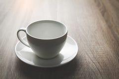 Fermez-vous vers le haut de la tasse de café blanc sur la table en bois noire près de la fenêtre Photographie stock
