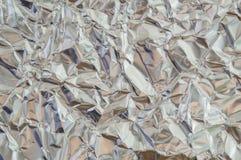 Fermez-vous vers le haut de la texture de fond de feuille argentée avec brillant chiffonné Photographie stock libre de droits