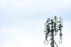 Fermez-vous vers le haut de la tour blanche de répétiteur d'antenne de couleur sur le ciel bleu Image stock
