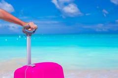 Fermez-vous vers le haut de la valise contre l'océan de turquoise et le ciel bleu Photographie stock libre de droits