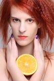 Fermez-vous vers le haut de la verticale de la femme redhaired avec la moitié orange Image stock