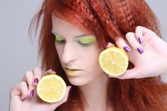 Fermez-vous vers le haut de la verticale de la fille redhaired avec le citron Photos libres de droits