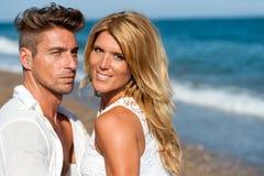 Fermez-vous vers le haut de la verticale des couples beaux sur la plage. Photographie stock