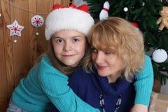 Fermez-vous vers le haut de la verticale Mère et fille de sourire avec des décorations de Noël Photographie stock libre de droits
