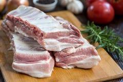Fermez-vous vers le haut de la viande crue de nervure de porc sur le conseil en bois avec un pot d'épices Photographie stock libre de droits
