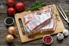 Fermez-vous vers le haut de la viande crue de nervure de porc sur le conseil en bois avec un pot d'épices Images stock