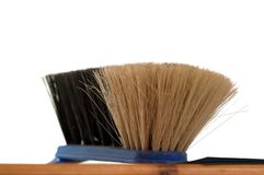 Fermez-vous vers le haut de la vieille brosse sur le plancher en bois sur un fond blanc image stock