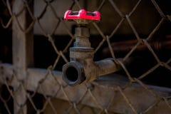 Fermez-vous vers le haut de la vieille valve de l'eau, de la valve de l'eau de rouille, et du tuyau dehors photographie stock libre de droits