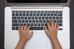Fermez-vous vers le haut de la vue aérienne des mains d'enfants dactylographiant sur l'ordinateur portable Photo libre de droits