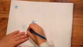 Fermez-vous vers le haut de la vue au dessin de la main d'enfant sur le papier Le dessin des étoiles avec corrigent clips vidéos