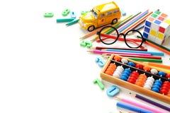 Fermez-vous vers le haut de la vue colorée de nouveau à la frontière de fournitures scolaires au-dessus de la table blanche Arith Photos stock