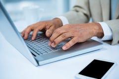 fermez-vous vers le haut de la vue d'un homme d'affaires utilisant son ordinateur portable Photo stock