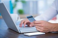 Fermez-vous vers le haut de la vue d'un homme d'affaires utilisant une carte de crédit Photos libres de droits