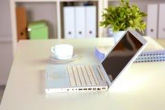 Fermez-vous vers le haut de la vue d'un intérieur de bureau de travail avec un ordinateur portable, une tasse de café et les ride Image libre de droits