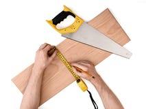 Fermez-vous vers le haut de la vue d'un man& x27 ; s remet la planche en bois de mesure avec la ligne de bande, d'isolement sur l Photos libres de droits