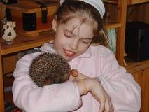 Fermez-vous vers le haut de la vue d'une jeune fille tenant un hérisson et un sourire mignons Image libre de droits