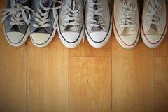 Fermez-vous vers le haut de la vue d'une ligne de plusieurs paires d'espadrilles de vintage sur un plancher en bois Image stock