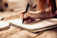 Fermez-vous vers le haut de la vue de l'écriture de la main de la femme avec le stylo sur le carnet sur la table en bois Image libre de droits