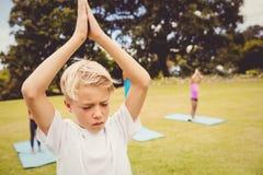 Fermez-vous vers le haut de la vue de l'enfant faisant le yoga avec des amis Photos stock