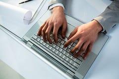 Fermez-vous vers le haut de la vue de l'homme d'affaires utilisant l'ordinateur portable Photographie stock libre de droits