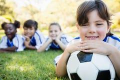 Fermez-vous vers le haut de la vue de la fille se trouvant sur le plancher avec son équipe de football Photos libres de droits
